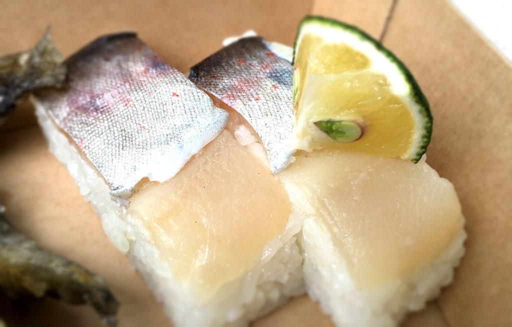 アナンタイジシェフの絶品エノハ寿司。天然手づかみで捕ってきたエノハ(マス)の押し寿司、大分県の特産カボスを絞って食べると恍惚の味わい。